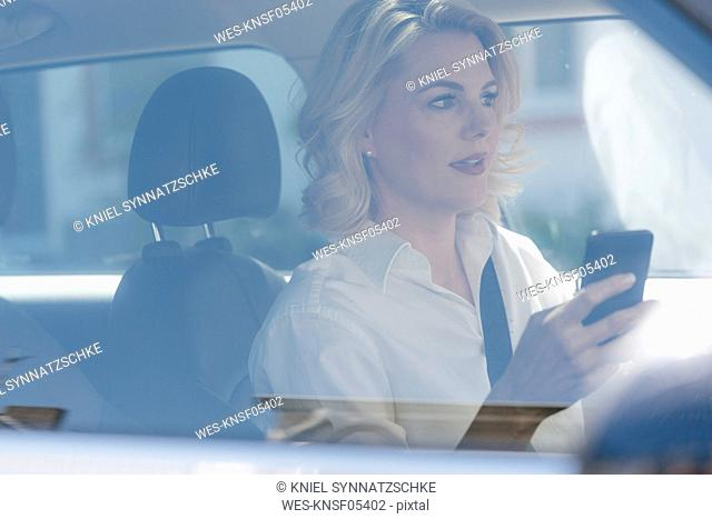Businesswoman using cell phone while driving car
