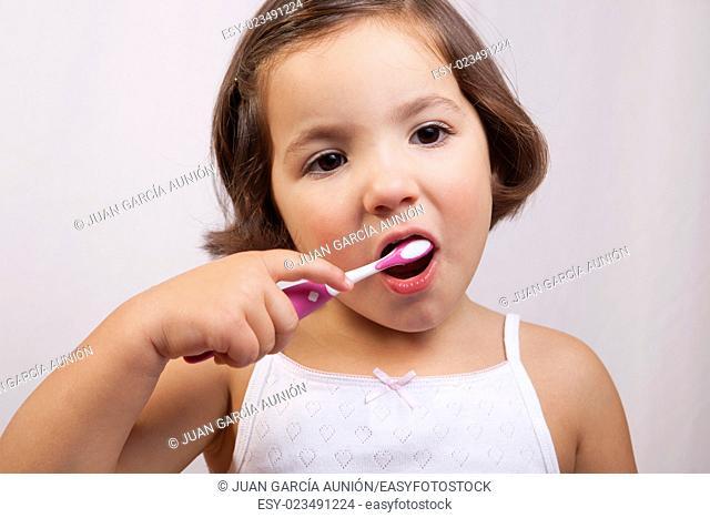 Little brown eye girl brushing her teeth. Isolated over white background
