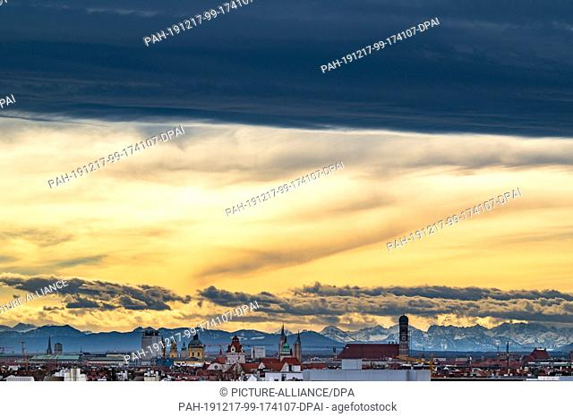 dpatop - 17 December 2019, Bavaria, Munich: A dark band of clouds hangs over the Bavarian capital, whose centre is marked by the high towers of the Frauenkirche...