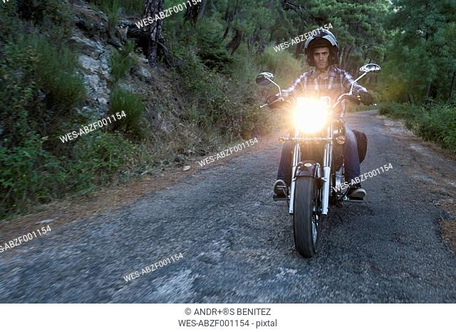 Man riding motorbike on country road