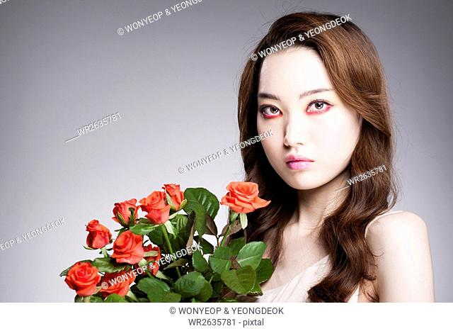 Portrait of young Korean woman in red eye liner posing with red roses