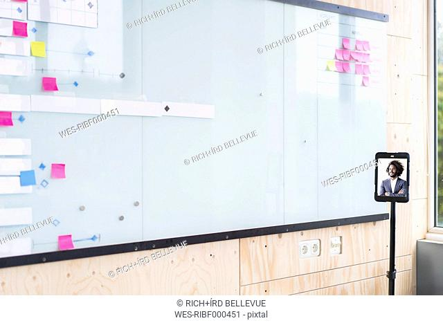 Video conference on digital tablet in front of concept wall
