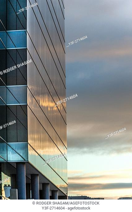 The clouds and the setting sun reflect off the windows of a high rise building