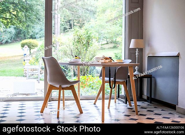 Interior view of breakfast on table by window at home