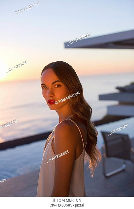Portrait serious, beautiful woman on sunset patio with ocean view