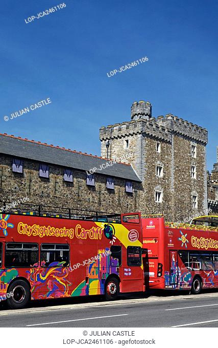 Wales, Cardiff, Cardiff. Open-topped double decker sightseeing tourist buses outside Cardiff Castle