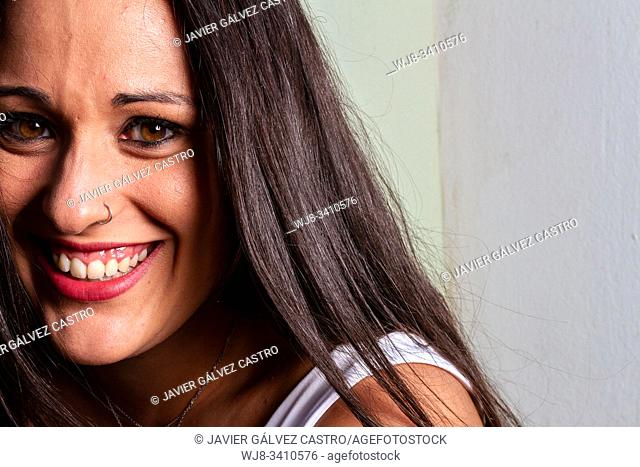 studio lighting portrait of a young woman smiling with expressive eyes