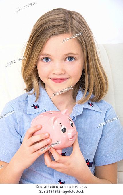 Little smiling girl holding a piggy bank