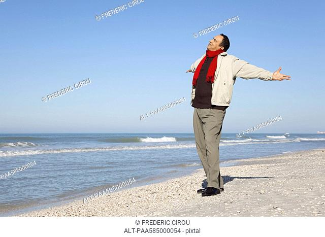 Man standing on beach with arms out and head back