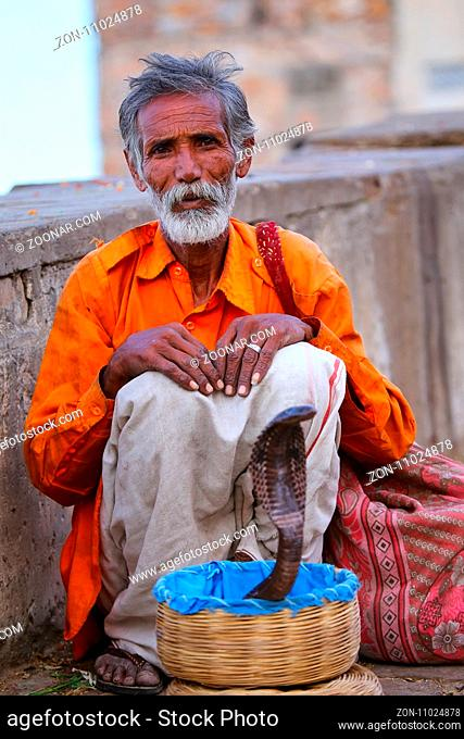 Local snake charmer sitting in the street of Jaipur, India. Jaipur is the capital and largest city of the Indian state of Rajasthan