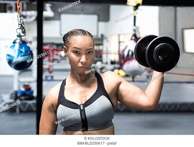 Black woman lifting dumbbell in gymnasium