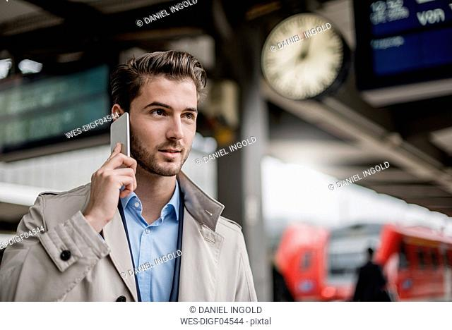 Businessman at the station on cell phone