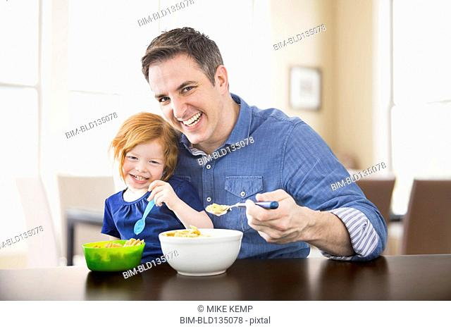 Caucasian father and daughter eating breakfast together