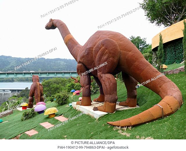 11 April 2019, US, Hillsborough: Dinosaur figures stand in front of a colourfully painted house in an unusual style in Hillsborough near San Francisco