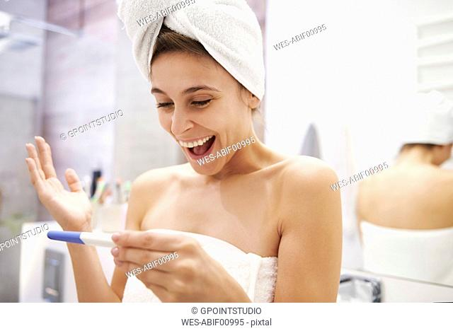 Portrait of excited young woman looking at pregnancy test in bathroom