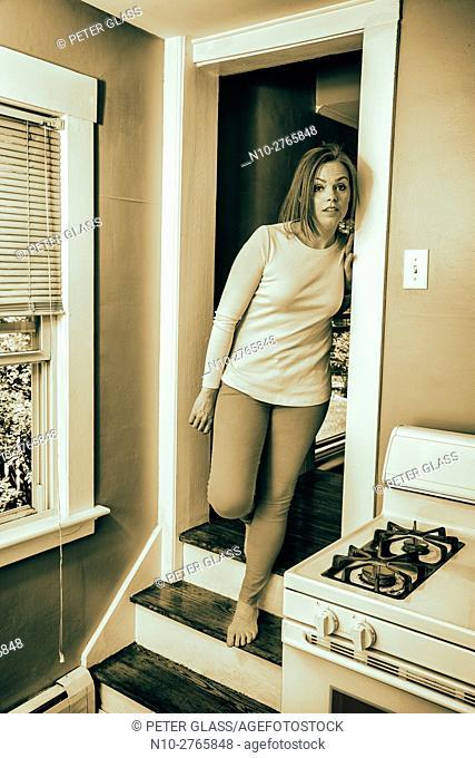 Young woman standing in her kitchen doorway