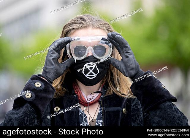 03 May 2020, Berlin: A participant of a rally of Extinction Rebellion at the Brandenburg Gate puts on protective goggles