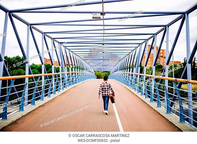 Gypsy boy with guitar walking across the bridge