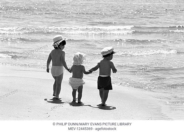 Three small children wearing sun hats hold hands in the sunshine and walk to the sea on the beach at Tenby, Wales. First publisdhed The Sunday Times