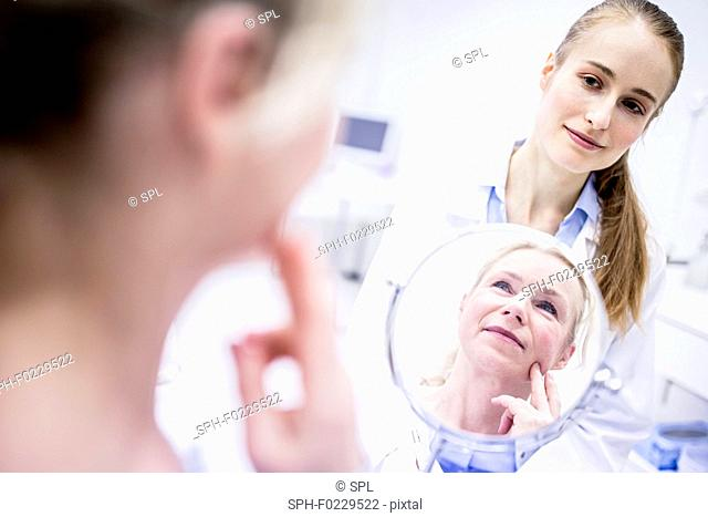 Mature woman looking into mirror