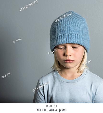 Portrait of boy wearing wool hat looking sad