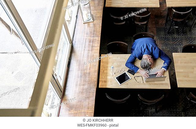 Exhausted mature businessman in cafe with laptop, tablet and cell phone