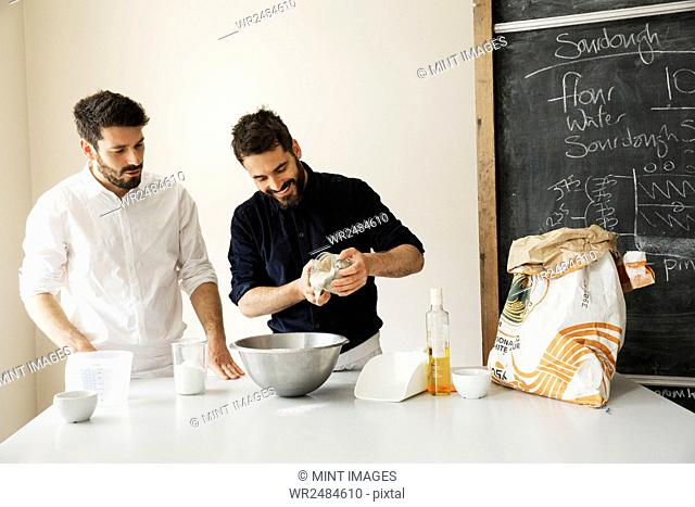 Two bakers standing at a table, preparing bread dough, baking ingredients and a blackboard on the wall