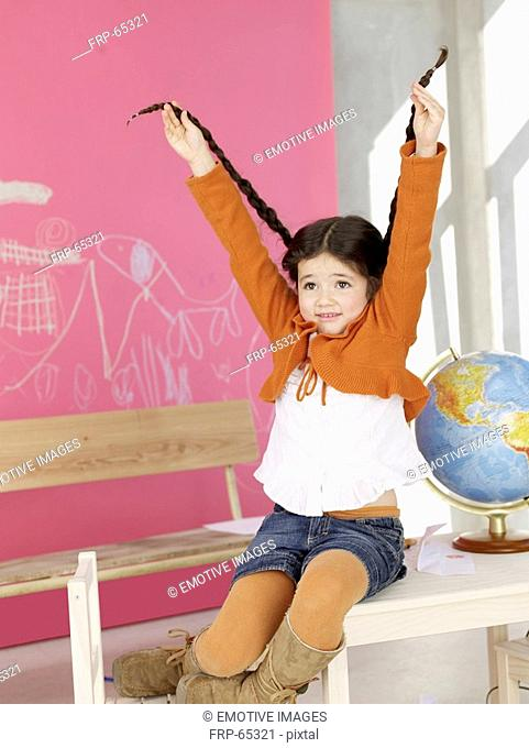 Girl sitting on the table next to globe lifting her plait
