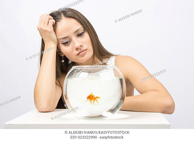 A young girl sits next to a round aquarium in which swimming goldfish