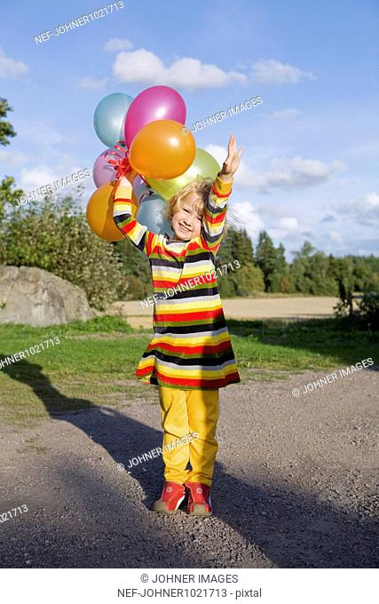 Girl holding balloons and raising hand
