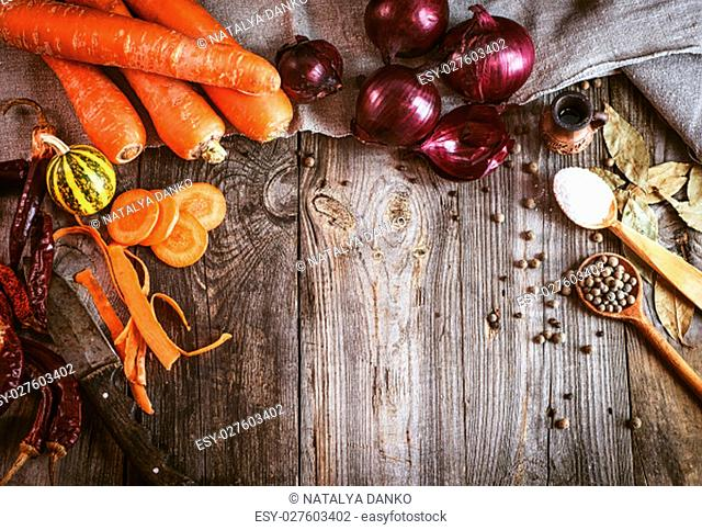 Fresh raw vegetables and spices on gray wooden surface, empty space in the middle, vintage toning