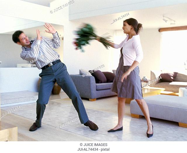 View of woman attacking boyfriend with flowers