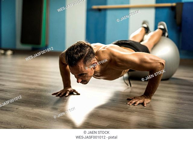 Man doing push-ups with fitness ball in a gym