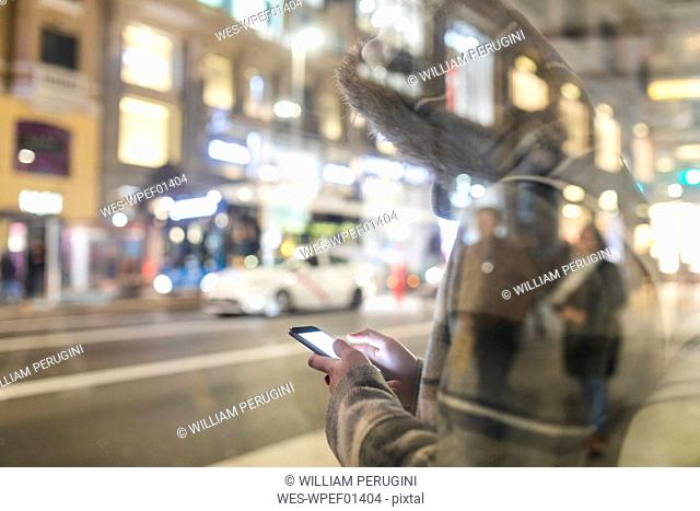 Spain, Madrid, young woman in the city at night next to Gran Via using her smartphone