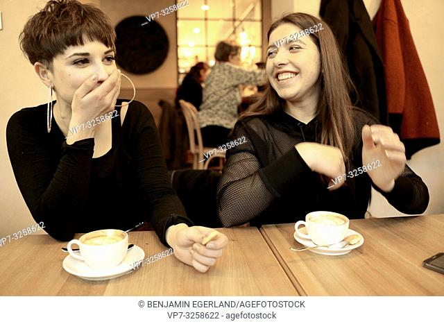 best friends teasing while enjoying coffee and biscuit in café restaurant, afternoon coffee break, in Germany