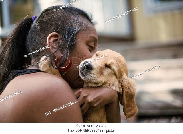 Woman kissing puppy