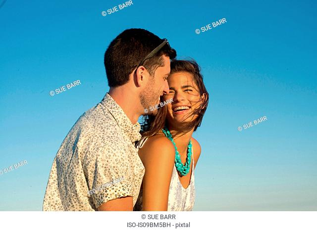 Romantic young couple laughing against blue sky