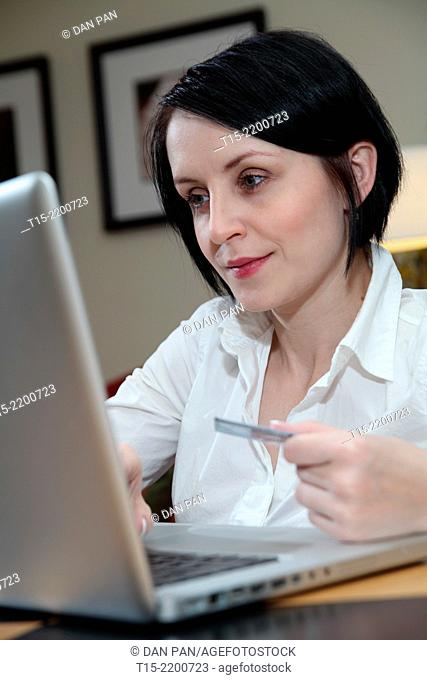 A black haired young woman shopping on the internet