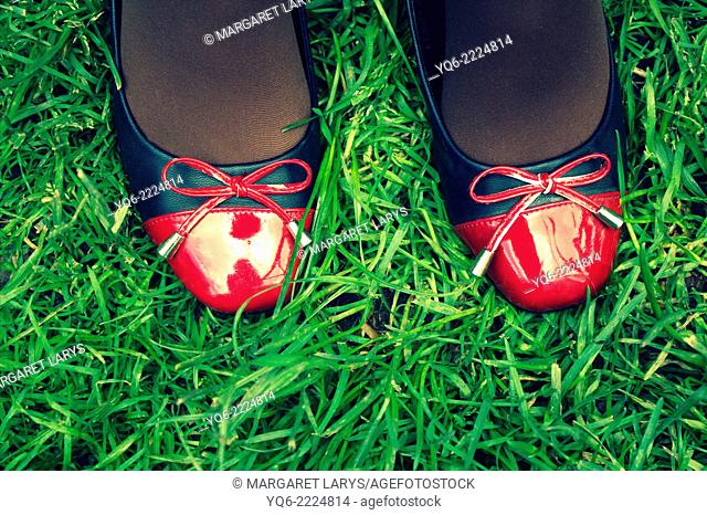 A teenager's legs in red and black shoes on the grass