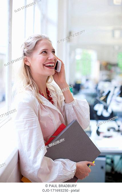 Smiling businesswoman holding folders and talking on cell phone in office