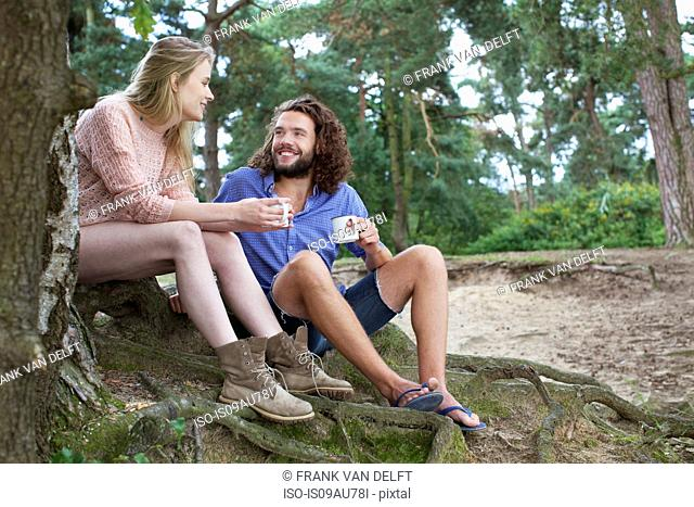 Young couple chatting beside tree