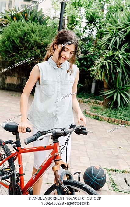 Cute adolescent taking her bike from backyard