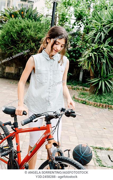 Cute adolescent taking her bike from backyard