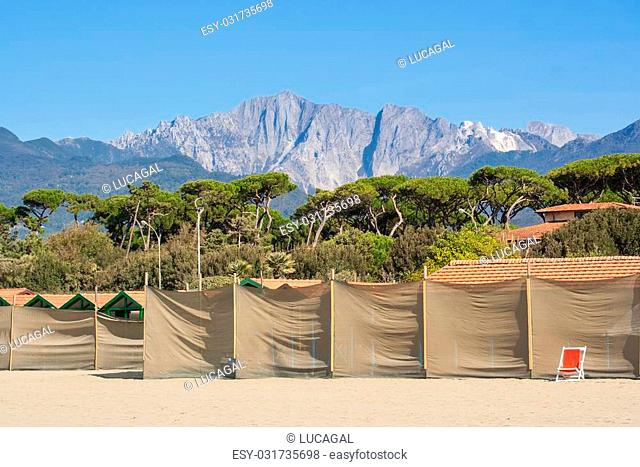 """""""""""""""""""""""monte altissimo"""""""" mountain of apuan alps viewed from forte dei marmi' s beach in winter. beach cabin protected by fabric sheets"""