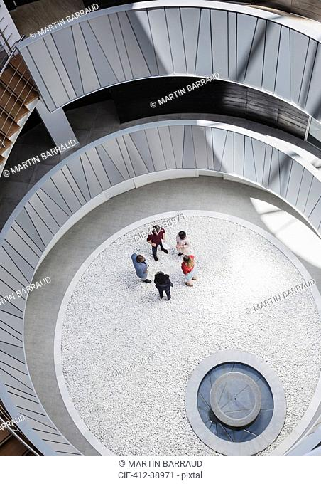 View from above business people talking in round, modern office atrium courtyard