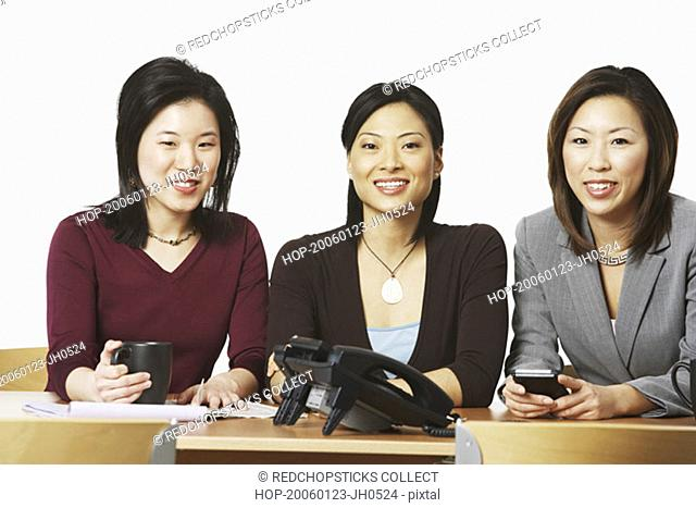 Portrait of three businesswomen sitting and smiling