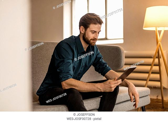 Young man sitting on the couch using tablet