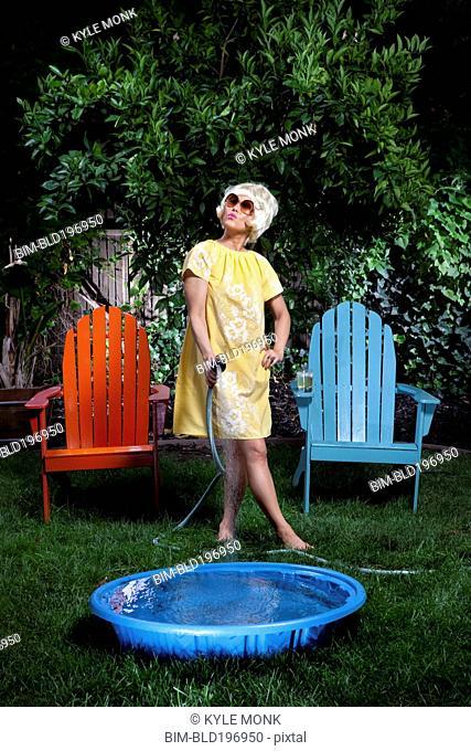 Korean woman filling up small pool in backyard