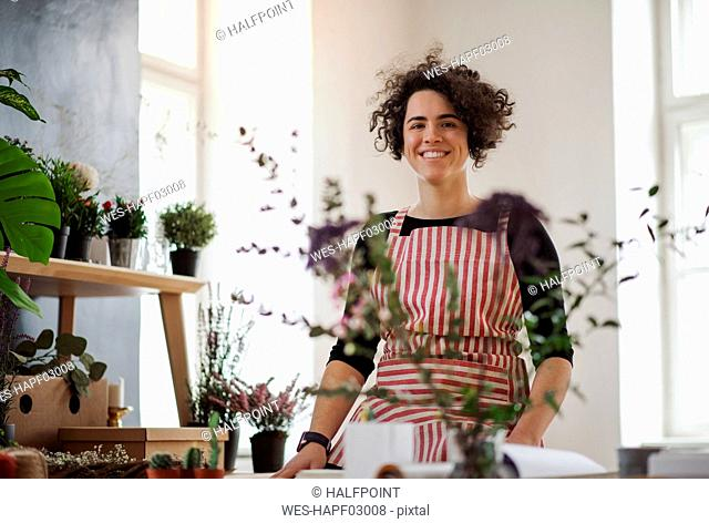 Portrait of smiling young woman in a small shop with plants