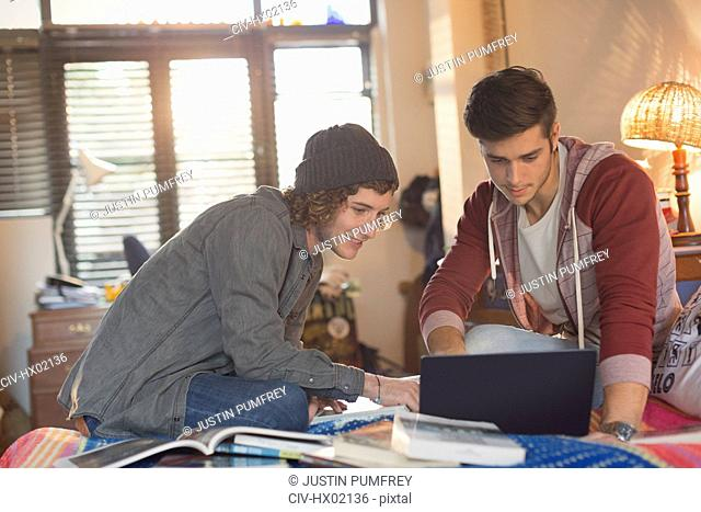 Young men college students studying using laptop